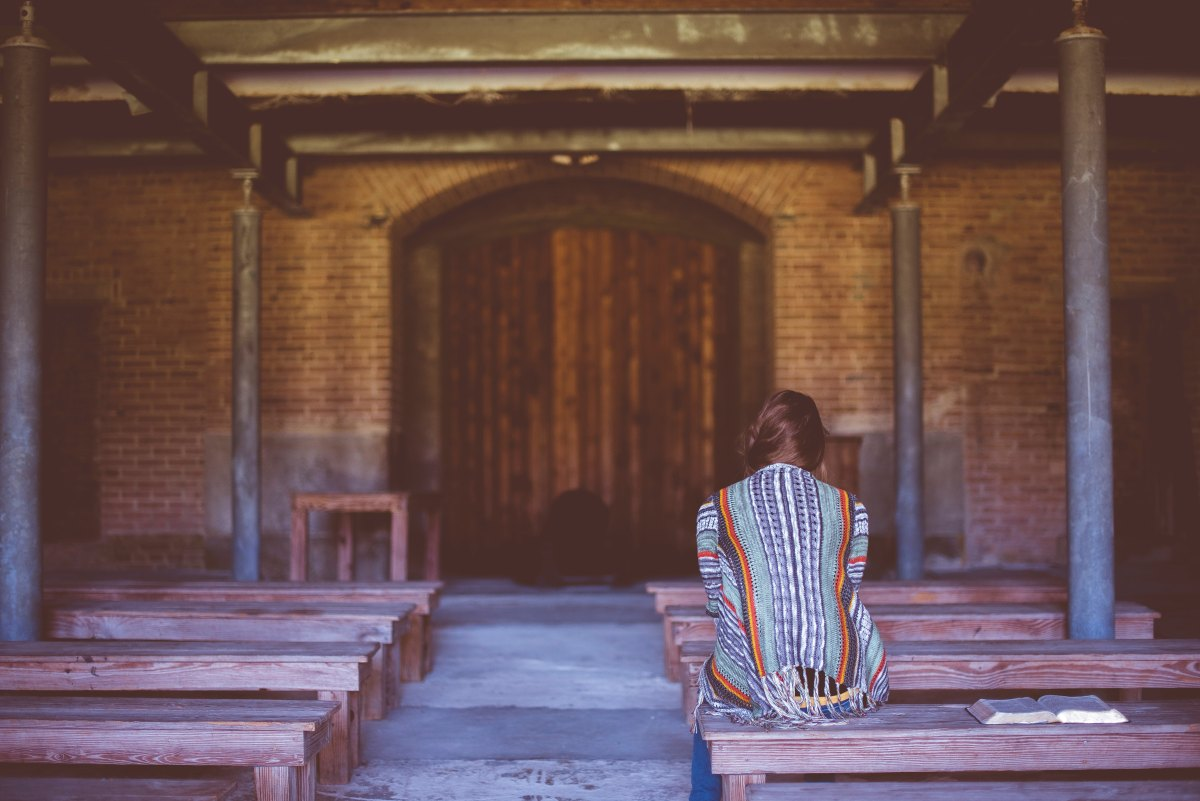 woman sitting on bench praying