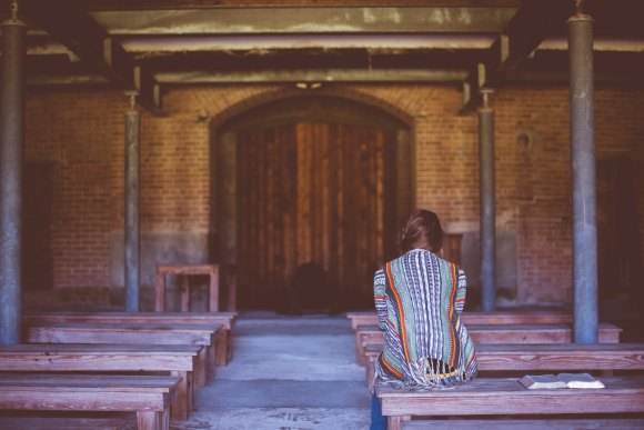 woman sitting on bench praying