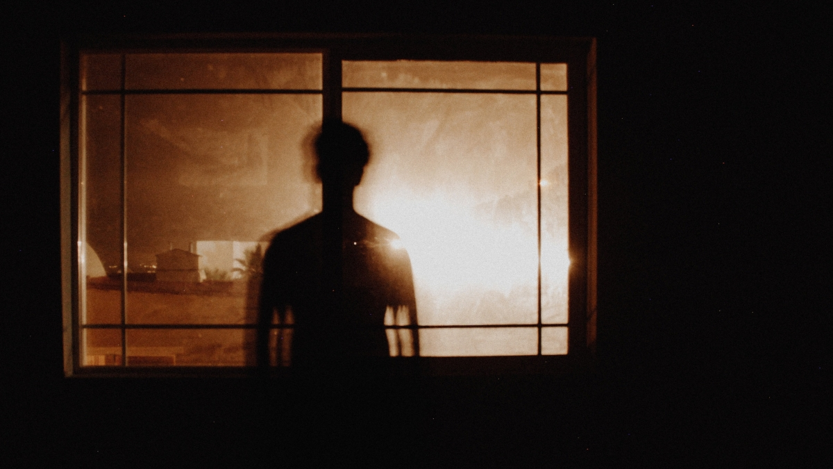 Person standing before window in dark room looking at bright light.