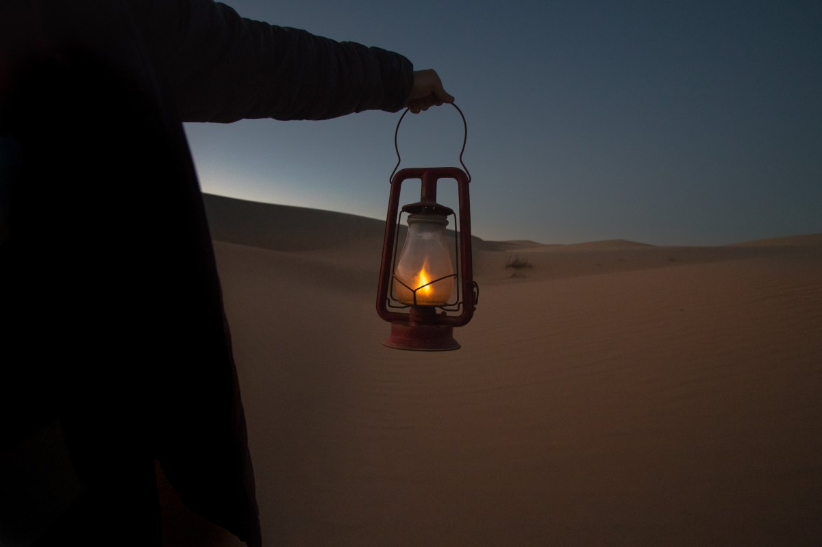 Person holding lantern in dark desert