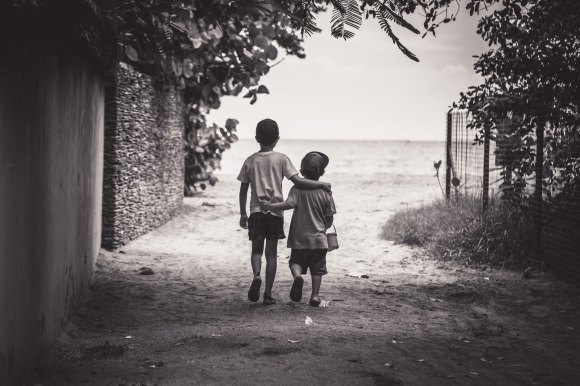 Two young boys walking away arm-in-arm