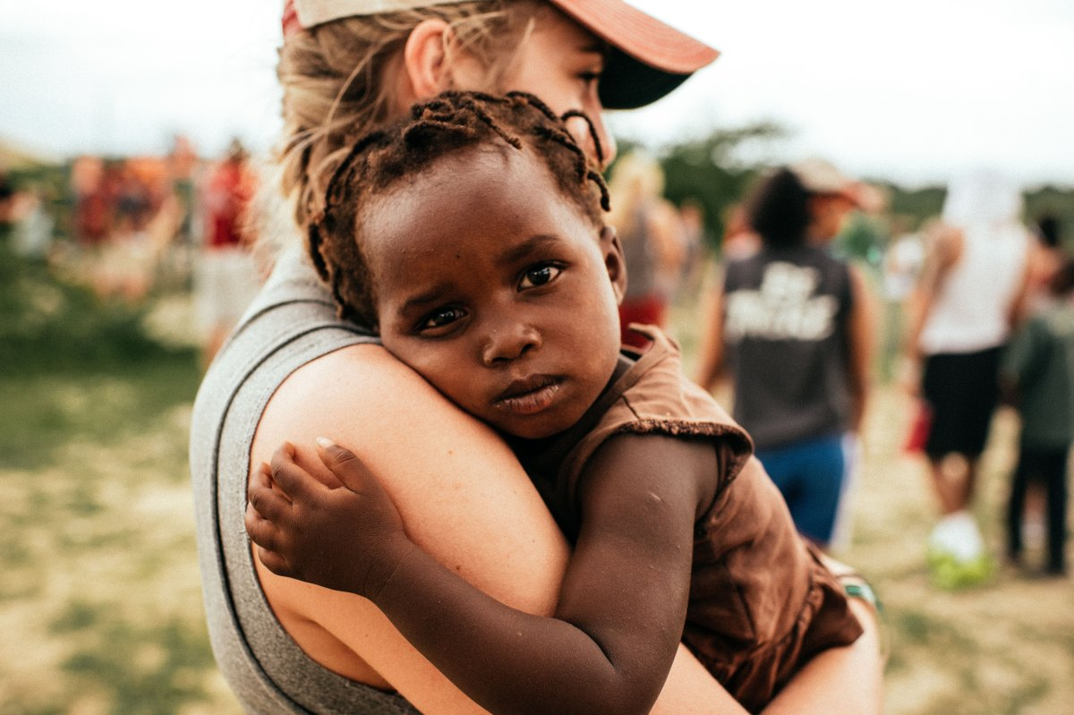 Young woman holding Haitian child.