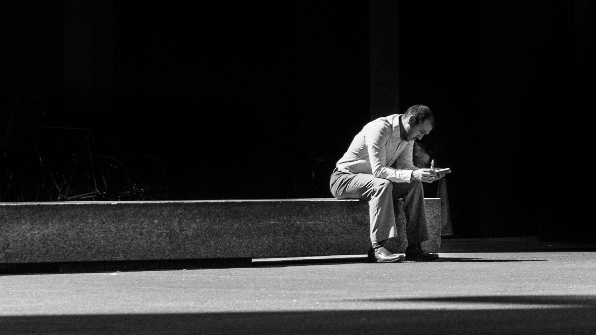 Man sitting and praying at and of long concrete bench.