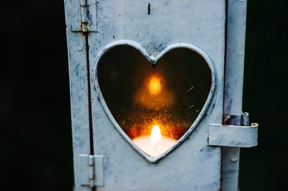 box with heart-shaped window revealing a candle within