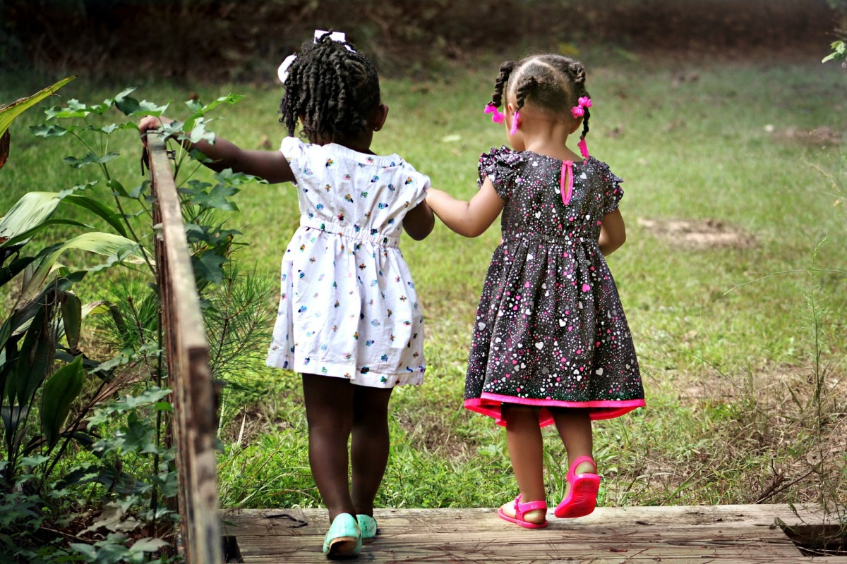 two toddler girls walking together