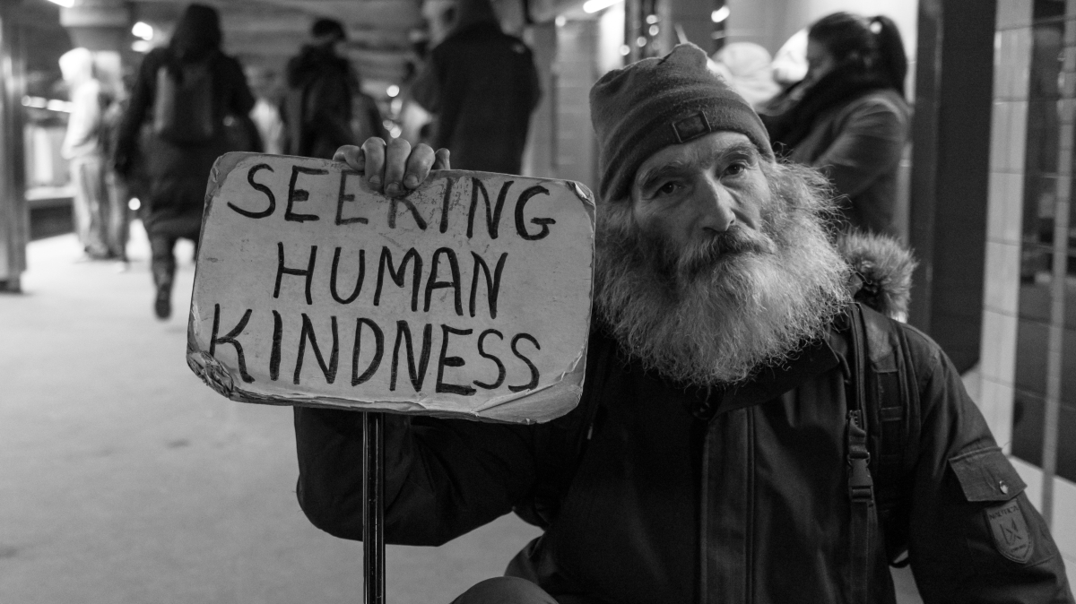 "homeless man with sign saying ""seeking human kindness"""