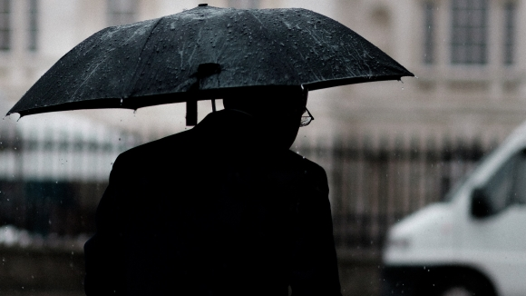 man walking in rain with black umbrella