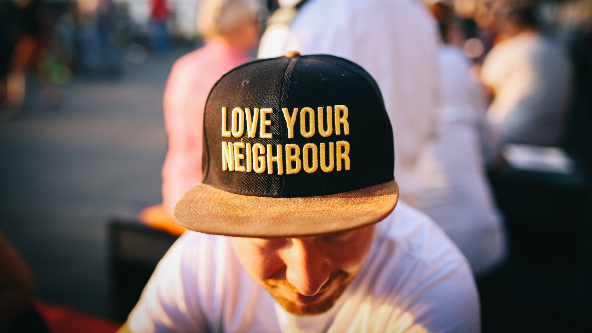 Young man wearing hat that says Love Your Neighbor.