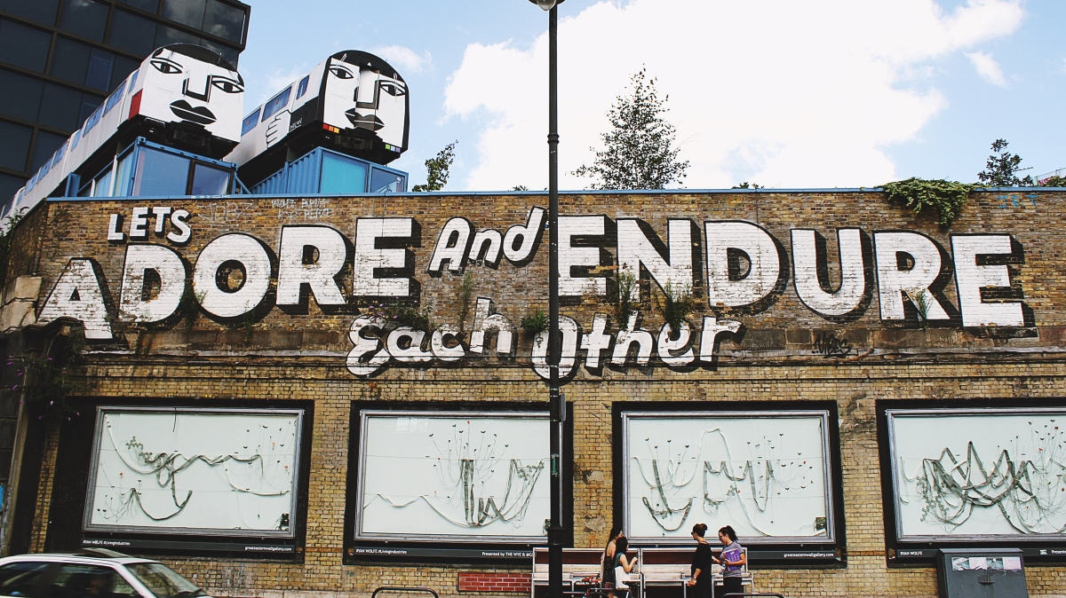 """side of building painted with words """"Lets adore and endure each other"""""""