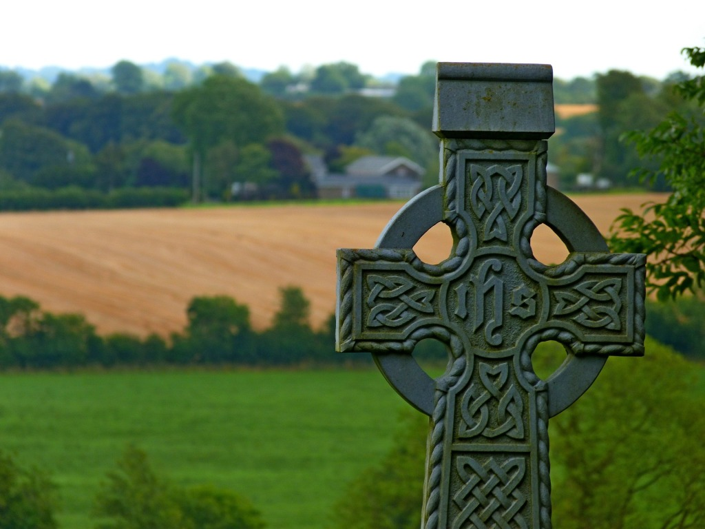 Stone Irish cross in rural landscape